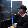 Jeff Channel, of Angie's BACKROAD BBQ, checks the ribs for the People's Choice competition during Smokin' Red Dirt BBQ contest Friday April 21, 2017 in downtown Enid. (Billy Hefton / Enid News & Eagle)