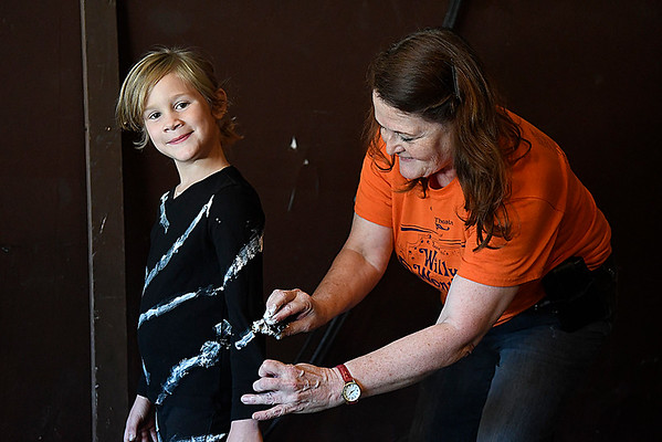 "Autumn Rogers smiles as instructor, Terri Galer, paints stripes on her costume for the Gaslight Kids' Drama Camp production of the ""Lion King Kids"" at the Gaslight Theater. (Billy Hefton / Enid News & Eagle)"