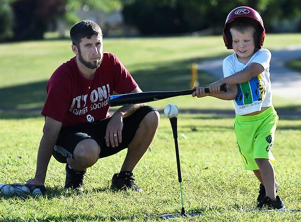 Brandon Barnett watches his son, Blanton, takes some swings Friday May 12, 2017 at Crosslin Park. (Billy Hefton / Enid News & Eagle)