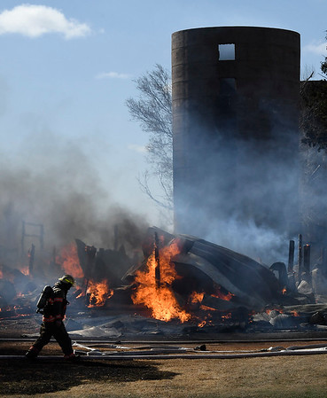 A firefighter walks pass a burning barn on south 30th Friday February 24, 2017. (Billy Hefton / Enid News & Eagle)