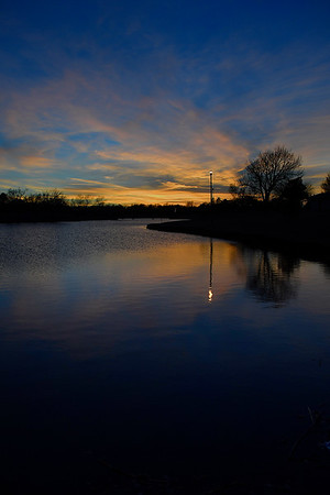 A light pole is reflected on the water of Meadowlake Park at sunset Wednesday February 1, 2017. (Billy Hefton / Enid News & Eagle)