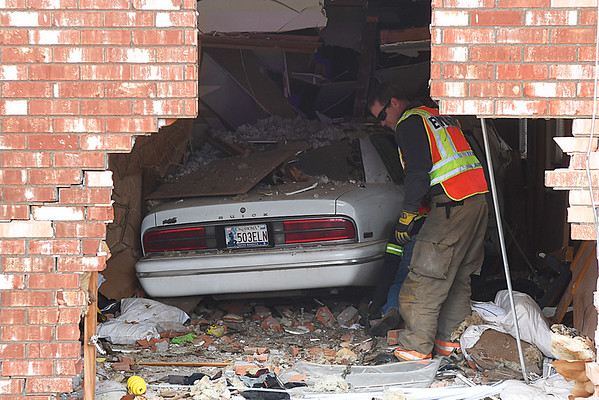 An Enid firefighter looks over a car that drove into the house 201 N. McKinley Wednesday January 18, 2017. (Billy Hefton / Enid News & Eagle)