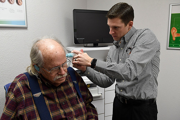 Kyle Kuykendall, B.U.S., works with a patient at the Kuykendall Hearing Aid Center January 20, 2017. (Billy Hefton / Enid News & Eagle)