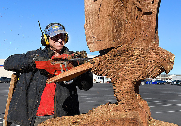 Clayton Coss uses a chainsaw to carve an eagle from an old tree in the El Patio parking lot on west Garriott Wednesday February 15, 2017. (Billy Hefton / Enid News & Eagle)