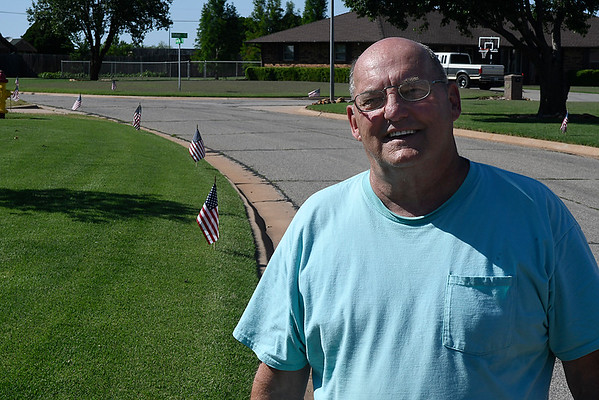 Don Von Hagel stands next to some the 96 flags he placed along Gray Ridge Rd. in honor of Memorial Day. (Billy Hefton / Enid News & Eagle)