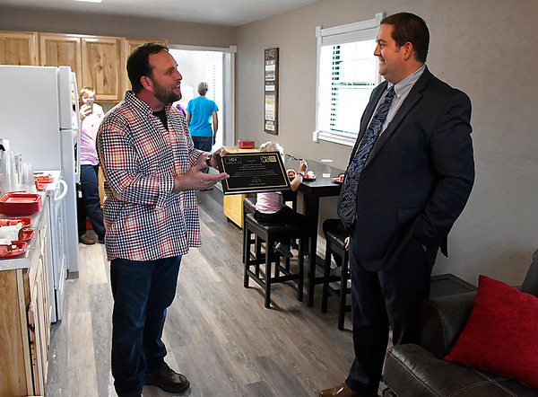 Rodney Fowler presents Aaron Abbott of Leadership Greater Enid with a plaque of appreciation during an open house for the Hope Outreach Women's Transitational Housing facility Thursday April 20, 2017. (Billy Hefton / Enid News & Eagle)