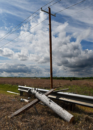 A portion of a down utility pole leans against a guard rail along Holden Road between Stabe and Sheridan Roads Wednesday May 3, 2017. (Billy Hefton / Enid News & Eagle)