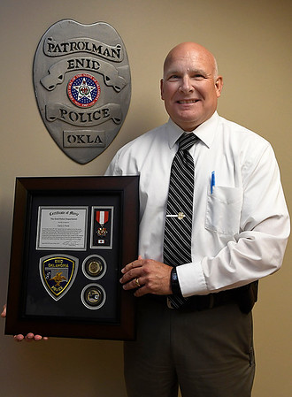 Capt. Gary Fuxa holds a life saving award from the Enid Police Department. (Billy Hefton / Enid News & Eagle)
