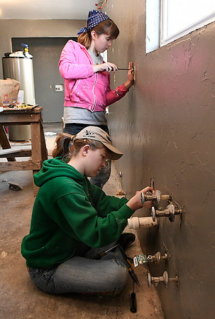 Marquette University students, Emma Nitschke and Emmale Hanson, install new outlets at a house being remodeled by Habitat For Humanity Tuesday March 14, 2017. (Billy Hefton / Enid News & Eagle)