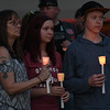 (left to right) Teresa Bridges, Kaitlyn Cushman and Nate Keith hold candle during a memorial service for Enid's Baby Boy Angel Friday April 14, 2017 at the Garfield County Courthouse gazebo. (Billy Hefton / Enid News & Eagle)