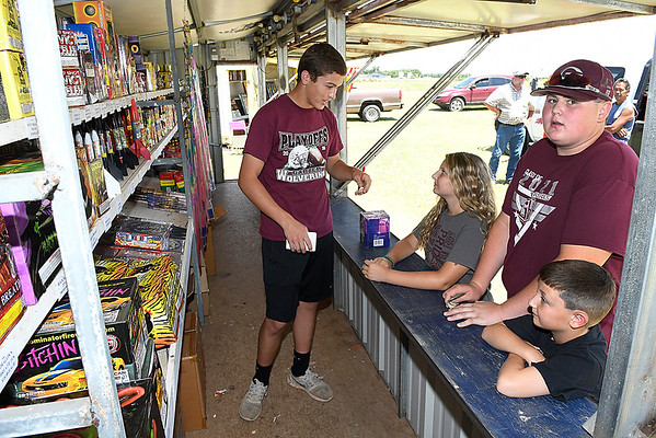 Koda Oller assist Anndi, Kennon and Gunner Sharp in picking fireworks at the Breckinridge Fire Department's firework stand Saturday July 1, 2017. (Billy Hefton / Enid News & Eagle)