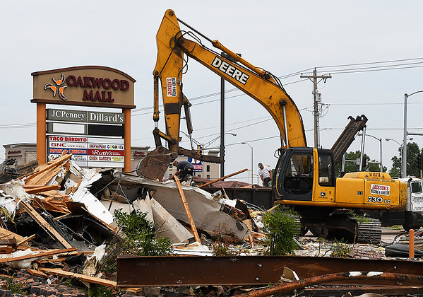 A tract hoe cleans the debris from the former Blockbuster location in front of Oakwood Mall Wednesday July 26, 2017. (Billy Hefton / Enid News & Eagle)