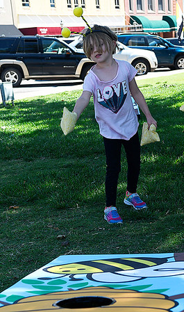 Kaylee tries the bean bag toss during the Bee Invasion Saturday May 13, 2017 on the Garfield County Courthouse lawn. (Billy Hefton / Enid News & Eagle)