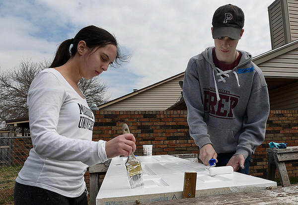 Marquette University students, James Niland and Alyssa Palumbo, paint a door for a house being remodeled by Habitat For Humanity Tuesday March 14, 2017. (Billy Hefton / Enid News & Eagle)