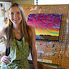 Catherine Freshley stands next to one of her paintings in her studio May 25, 2017. (Billy Hefton / Enid News & Eagle)
