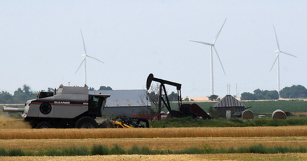 A combines harvest a field north of Fairmont Friday June 2, 2017 showing three industries of northwest Oklahoma agriculture, oil and wind. (Billy Hefton / Enid News & Eagle)