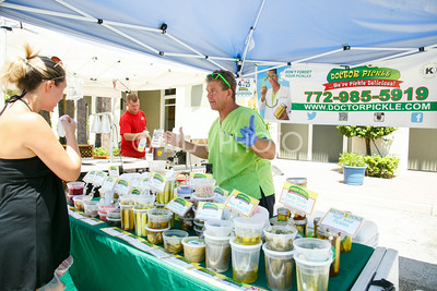 "Harold Pitts, ""Doctor Pickle"", helps Ashley St. Clair with his samples at the Summer Gardens GreenMarket at STORE Sunday."