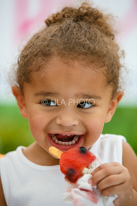 Chailyn Still, 2, enjoys a natural ice pop at the Mom's Pops stand in the Summer Gardens GreenMarket at STORE Sunday.