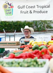 Curtis Johnson sits in his Gulf Coast Tropical Fruit and Produce stand in the Summer Gardens GreenMarket at STORE Sunday.