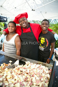 Kevin Bazile stands with his sons Kenny, 13, left, and Macklee, 16, at his K. Malou Caterers stand in the Summer Gardens GreenMarket at STORE Sunday.