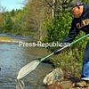 ALVIN REINER/ P-R PHOTO<br /> Newman Tryon releases brown trout into the Boquet River in Essex County. He was one volunteer who recently helped Nicole Cain, a fish culturist from the State Department of Environmental Conservation, to stock the waterway from the fish hatchery near Caledonia in Livingston County. The trout were released at several spots in the towns of Lewis and Elizabethtown.