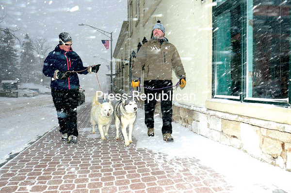 JACK LADUKE/ P-R PHOTO<br /> Annette and Cliff Ripelle of Ottawa, Ontario, walk their two Siberian huskies in downtown Lake Placid. Because of the massive snowstorm that hit Tuesday, the couple decided to stay an extra day to take advantage of the fresh snow and go cross-country skiing again today.