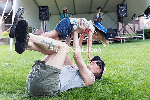 GABE DICKENS/ P-R PHOTO<br /> Plattsburgh resident Travis Collins and his 2-year-old daughter Cassidy frolic on the front lawn of the Strand Center for the Arts as the band Ausable Branch, consisting of Cliff Reynolds and Heath Richman, perform on stage during Downtown Rising Saturday afternoon in Plattsburgh. The weekly event, which runs from 9 a.m. to 2 p.m. every Saturday through August, features local food and arts vendors and music, with Kevin Sabourin performing June 17 and Eddy and Kim Lawrence, June 24.