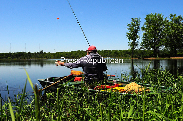 """KAYLA BREEN/ STAFF PHOTO<br /> Paul Marbut reels in his line after a successful morning of fishing at Ausable Marsh in Peru. """"I only caught one fish, but one is better than none,"""" he said."""