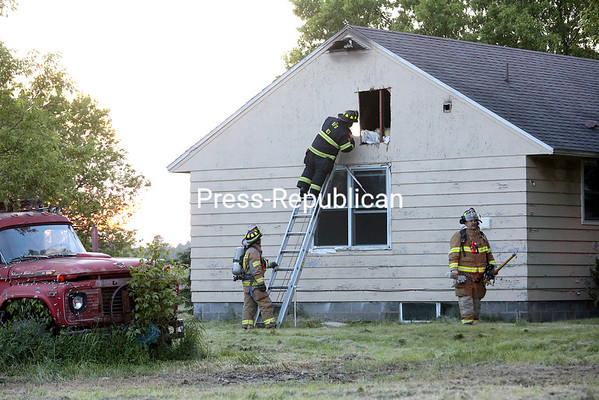 GABE DICKENS/ P-R PHOTO<br /> A firefighter peers into a house at 439 Moffitt Road in the Town of Plattsburgh following a fire there Wednesday evening. Clinton County Dispatch put out a call for the fire at 7:50 p.m. with Beekmantown and Cumberland Head volunteer fire departments responding. Mutual aid was provided by departments from West Chazy, Cumberland Head, South Plattsburgh and District 3 with Chazy and Cadyville departments on standby. Around 8:15 p.m., a firefighter said in a radio report over the scanner that the fire was mostly under control and that overhauling had begun. The firefighter remarked that the fire had been largely knocked down by the time crews arrived. The home is owned by William Castine Jr., according to the Clinton County Real Property Office website. Beekmantown was back in service at 9:49 p.m.