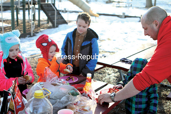 MIKE PITTS/ P-R PHOTO<br /> It was warm enough for a winter-break cookout for this family at Melissa L. Penfield Park in the City of Plattsburgh on Wednesday, but not enough to do away completely with warm hats and jackets. Enjoying grilled hot dogs served up by dad, Bryan Clausen, are Mariah Clausen, 7 (from left); Brice Clausen, 5; Dawson LaFountain, 8; and, Kayden Clausen, 3. Friend Justin Friedrich (not shown) did the grilling.