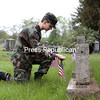 GABE DICKENS/ P-R PHOTO<br /> Dylan Coryer, a cadet in the James P. O'Connor Composite Squadron of the Civil Air Patrol, places an American Flag near the grave of Vernon E. Dandrow, who served as an Army Corporal in World War II, at Riverside Cemetery in Plattsburgh Friday afternoon. Sponsored by the American Legion Post 20, legion members, along with cadets, firefighters and hospital employees, volunteered their time to place flags at the graves of well over 100 American soldiers interred at Riverside, St. Peter's and Mt. Carmel cemeteries in advance of today's Memorial Day commemorations.