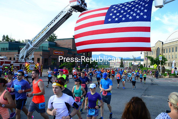JACK LADUKE/ P-R PHOTO<br /> Hundreds of runners pass under the large American flag stretched across the street in front of the Olympic Complex in Lake Placid Sunday for the annual Lake Placid Marathon and Half Marathon. About 1,200 athletes signed up for the event. Warm weather and sunny skies greeted the runners for the 8 a.m. start.