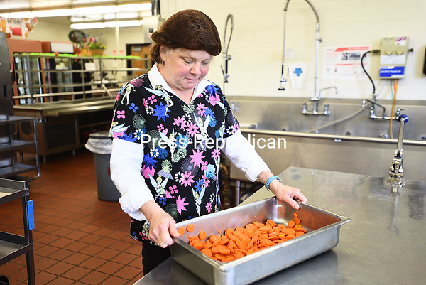 KAYLA BREEN/ STAFF PHOTO<br /> Cafeteria worker Maureen Harrigan prepares sliced carrots to be offered to students as a vegetable option during lunch at Plattsburgh High School. The Trump administration is canceling some of the changes that would have been required by federal law to schools that offer free and reduced-price meals, which is every public school in the North Country.