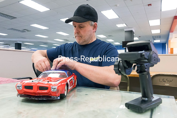 GABE DICKENS/ P-R PHOTO<br /> At his new location in Champlain Centre mall in Plattsburgh, Greg Nephew, owner of Lake City Hobbies, works on his vintage Trans-Am 1/10th scale radio-controlled road car, which is a 4-wheel belt-drive drive model with a graphite chassis created to be an accurate replica of a full-sized Trans-Am. Lake City Hobbies is located in the former Borders Books store.