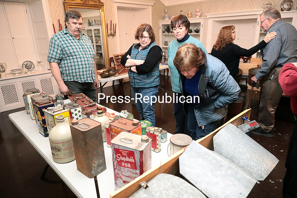 GABE DICKENS/ P-R PHOTO<br /> Ricky Laurin (left) of Chazy stands over his collection of antique maple syrup paraphernalia, which includes wooden and metal tree taps, collection buckets and tin and glass maple syrup cans and bottles, while (starting second from left) Maggie Carter, Maureen Robinson and Patricia Parker look over his wares during the recent Show and Tell Your History event, featuring Chazy Town Historian Robert Cheeseman, at the Alice T. Miner Museum in Chazy. Laurin has roughly 50,000 pieces of antique farm equipment at his home, which he has collected over the course of more than 30 years.