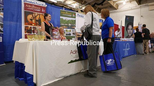 KAYLA BREEN/ STAFF PHOTO<br /> Alyssa Senecal (left) and Alina Walentowicz of the Adirondack Coast Visitors Bureau talk to Marion Daniels (left) and Kathy Snow about their booth during the recent North Country Chamber of Commerce Business Expo at the Plattsburgh State Field House. A total 161 businesses and exhibitors participated in the event, now in its 29th year.