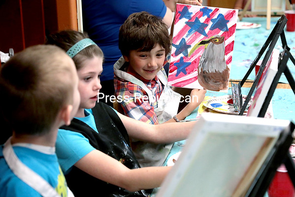 GABE DICKENS/ P-R PHOTO<br /> Peru Elementary School second-graders (from left) Austin Timmons, Brooke Taptick and Parker Lumb compare their patriotic paintings in Bette Crowningshield's class Friday afternoon. Artist Jesse Furnia of AuSable Forks instructed 140 second-graders at Peru in creating the artwork, which will be on display at the school during an end-of-the-year patriotic celebration, which will also feature music and classrooms set up as museums, from 6 to 7:30 p.m. Wednesday, June 7.
