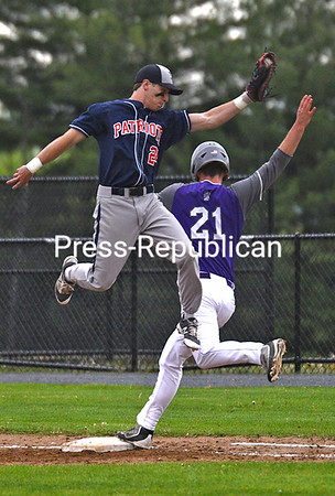 KAYLA BREEN/ STAFF PHOTOS<br /> AuSable Valley's Brandon Snow jumps for the baseball as Ticonderoga's Sam Dushane crosses first base.