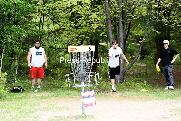 KAYLA BREEN/ STAFF PHOTO<br /> Tanner Rascoe tosses his Frisbee into the target basket while players Zach Laduke (left) and Nick Dodd watch during the Geoff Brenno Throw & Grow Disc Golf Tournament Sunday at Cadyville Recreation Park in Cadyville. Proceeds from the event benefited the Geoffrey A. Brenno Scholarship Fund.