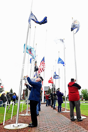 KAYLA BREEN/ STAFF PHOTO<br /> Disabled American Veterans members begin to raise the flags during the Raising of the Flags ceremony at the Plattsburgh Barracks Veterans Park on the U.S. Oval, part of the annual Memorial Day commemoration.