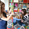 GABE DICKENS/ P-R PHOTO<br /> Ashley Kollar, a Cumberland Head Elementary School kindergarten teacher, captivates 10-monthold Rory with her musical talents while Mia, 3, entertains herself by sending stackers skyward at their home in Plattsburgh Saturday morning.