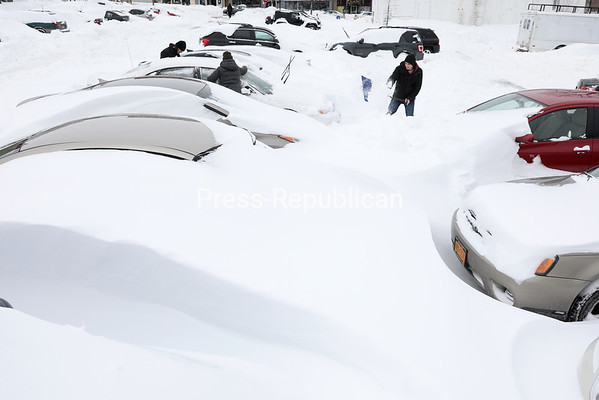 GABE DICKENS/ P-R PHOTO<br /> People dig out a car entombed in snow spread by winds in excess of 30 miles per hour in the Durkee Street parking lot in Plattsburgh Wednesday afternoon. Winter Storm Stella brought snowfalls of up to 34 inches to the North Country after originally being forecast to strike southern New York more severely. See more photos from Stella's snowy aftermath on Page A3.