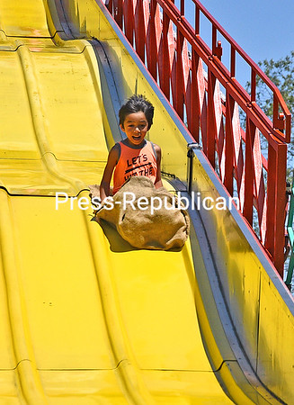 KAYLA BREEN/ STAFF PHOTO<br /> With a wide smile on his face, Cavan Tran, 6, slides down the Super Slide carnival ride at the Cadyville Fire Department Field Day. The event featured kid-friendly fun like carnival rides, games and a fire-safety trailer.