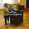KAYLA BREEN/STAFF PHOTO<br /> Mary Bell (left) feeds her ballot into the machine with the help of election clerk Tammy Fournia during Saranac Central School District's school budget vote Tuesday at Morrisonville Elementary School. People all over New York state weighed in on budgets, school-board candidates and propositions in annual votes.