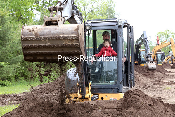GABE DICKENS/ P-R PHOTO<br /> Steve Coons, an employee of Upstate Materials, instructs 3-year-old Logan Gagliano of Montreal on how to operate an excavator during the 11th annual Dozerfest Saturday afternoon at Airborne Park Speedway in Plattsburgh. With the aid of professional operators, children had a chance to pilot and control various types of heavy machinery, take a ride high into the air in a lineman boom lift, operate a fire hose and much more. Sponsored by Plattsburgh Kiwanis Breakfast Club, the event has become the premiere fundraiser for various local children's programs.