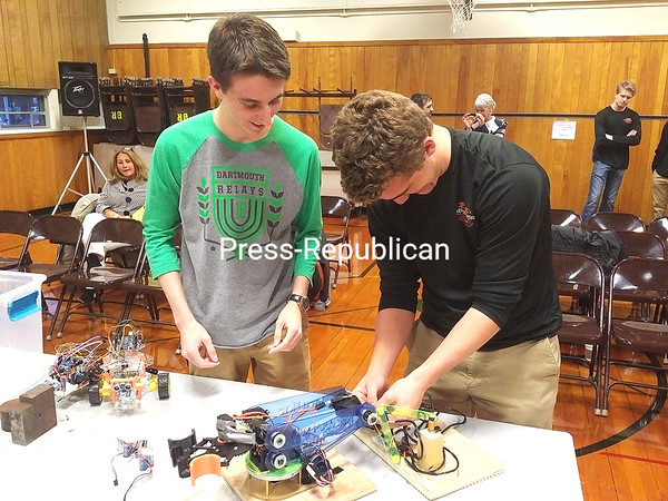 """ASHLEIGH LVINGSTON/ STAFF PHOTO<br /> At a recent Plattsburgh City School Board meeting, Plattsburgh High School students Ryan Flora (left) and Alex Puchalski (right) set up the device that earned them a third-place win in the """"Robot Arm"""" event at the Adirondack Science Olympiad Regional Tournament and an eighth-place win at the state Science Olympiad competition earlier this year."""