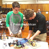 "ASHLEIGH LVINGSTON/ STAFF PHOTO<br /> At a recent Plattsburgh City School Board meeting, Plattsburgh High School students Ryan Flora (left) and Alex Puchalski (right) set up the device that earned them a third-place win in the ""Robot Arm"" event at the Adirondack Science Olympiad Regional Tournament and an eighth-place win at the state Science Olympiad competition earlier this year."