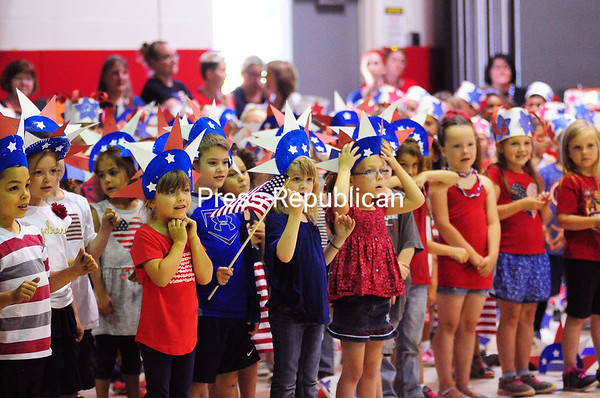 """KAYLA BREEN/ STAFF PHOTO<br /> Dressed head to toe in red, white and blue, Cumberland Head Elementary School students sing and sign the words to """"God Bless the USA"""" during a special Flag Day celebration in the school's gymnasium Wednesday. Different patriotic songs were performed by all grade levels with music teacher JoLee Yeddo leading the children in song and dance. See video with this photo at pressrepublican.com."""