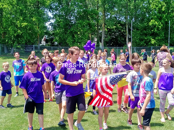 ASHLEIGH LIVINGSTON/ STAFF PHOTO<br /> Chazy Central Rural School sixth-grader Luke Moser carries the American flag as he leads a procession of students in pre-kindergarten through sixth grade around the district's soccer field Thursday as part of the school's Relay Recess. The event celebrated the fundraising efforts of the school's Kiwanis Kids, who raised $1,244 for the American Cancer Society and Relay for Life in memory of Kaleb LaBarge, a CCRS student who passed away from cancer in 2015.