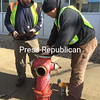 "SUZANNE MOORE/ STAFF PHOTO<br /> City of Plattsburgh Public Works employee Robby Calkins lowers a new gasket onto the fire hydrant in front of the Miller Street post office Wednesday afternoon while worker Justin Jock holds the top of the device. With more than 800 hydrants around the city, servicing is done on a two-year rotation in the wintertime, Jock explained. Gaskets are replaced as a matter of course, and, he said, ""If the bolts look a little shabby,"" they are switched out for new ones. ""The bolts are under tremendous pressure when the water comes on,"" Jock said."